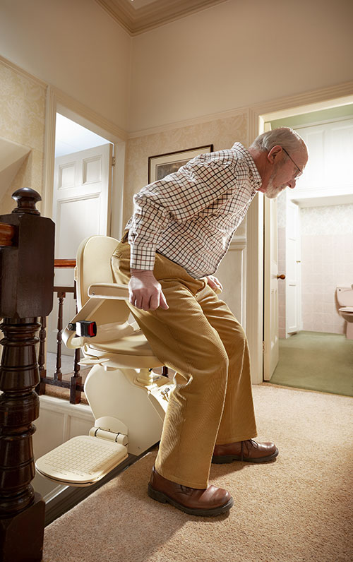 A Stairlift User Exiting Safely At The Top of Stairs